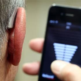 Man controling hearing aids from phone